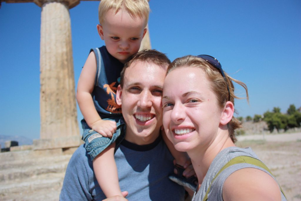 a man, woman, and boy take a selfie in front of the temple of apollo in corinth, greece