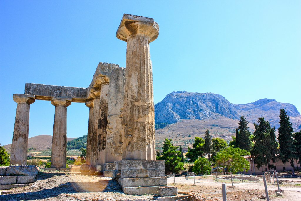 The ruins of the temple of apollo stands in front of the acrocorinth in the distance in corinth, greece