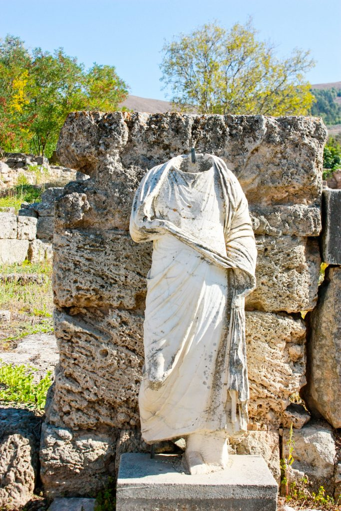 a headless statue stands outside in front of a stone wall in ancient corinth, greece