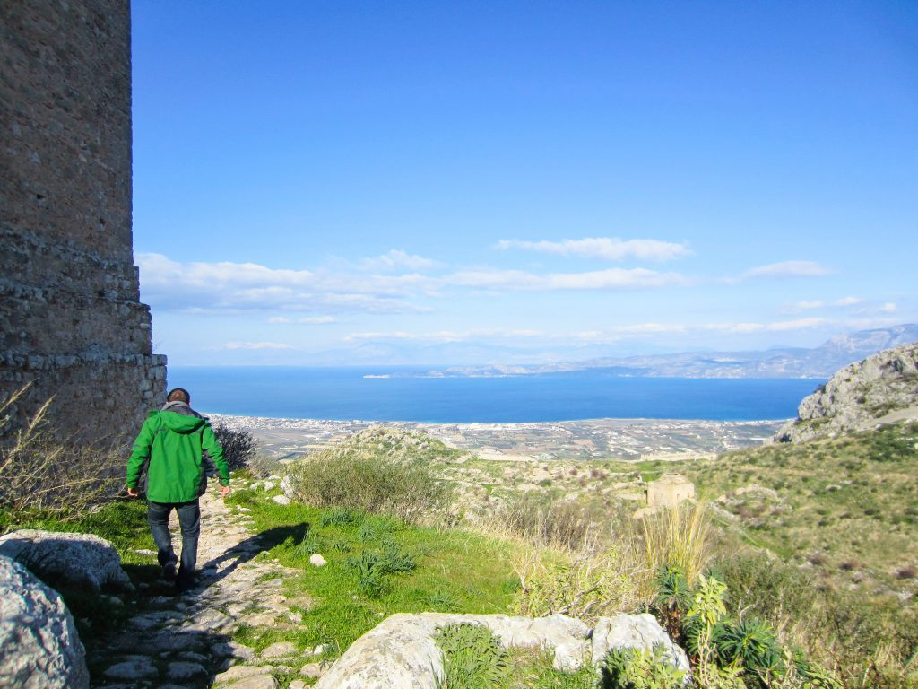 a man walks around a wall at the acrocorinth in corinth, greece