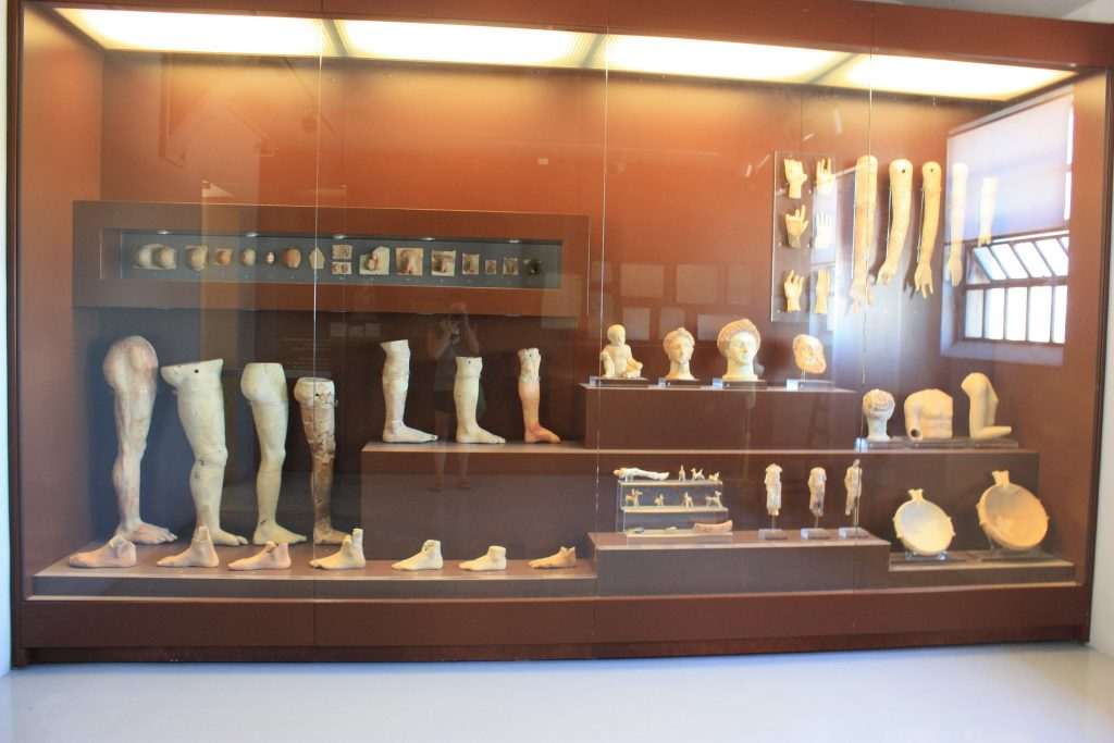 a display of clay body parts that were offered in the Sanctuary of Asklepieion as part of worship of Asclepios the greek god of medicine in corinth museum, greece