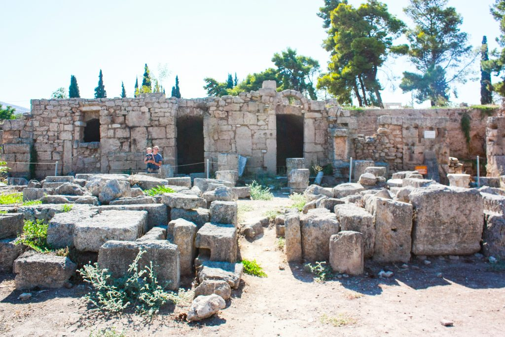 a man and a boy stand in front of a row of shop ruins and fallen stones in ancient corinth greece