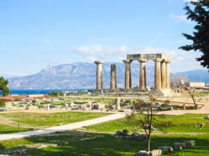 ancient corinth in greece, the temple of apollo stands amid some ruins with the gulf of corinth and the Geraneia mountains in the distance