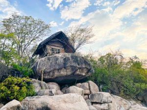 a reed and thatch lake chalet or tent sits on top of a large rock at Mumbo Island in Lake Malawi